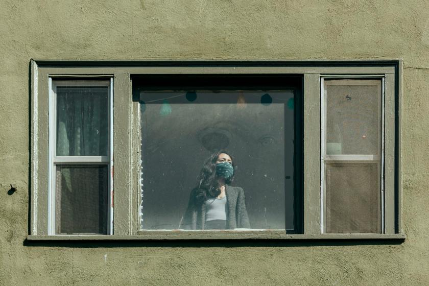 Woman covering her mouth with a bandana staring out the window during the coronavirus lockdown